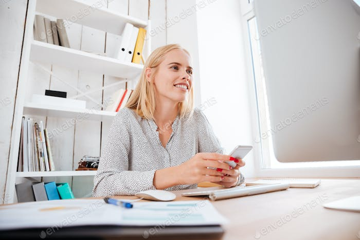 Businesswoman sitting at her workplace in office and holding phone