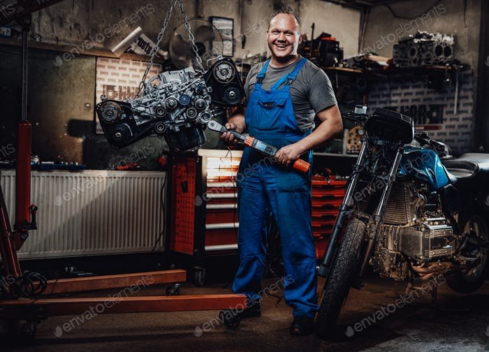 Professional mechanic stands next to the suspended flat engine and naked bike in garage