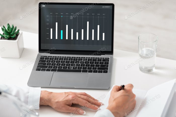 Female entrepreneur working with business chart on laptop screen, closeup
