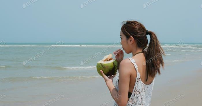 Frau trinken Kokosnuss am Strand
