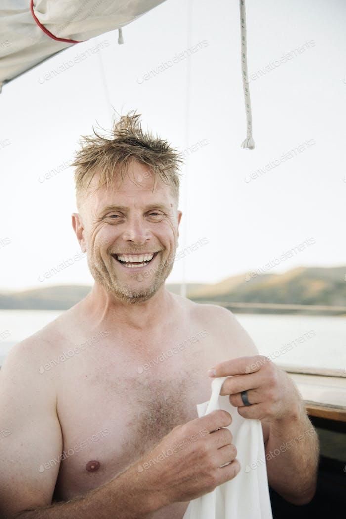 Smiling shirtless man standing on sail boat.