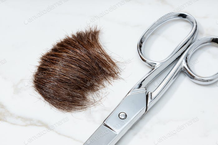 Brown Lock of hair and scissors on marble table