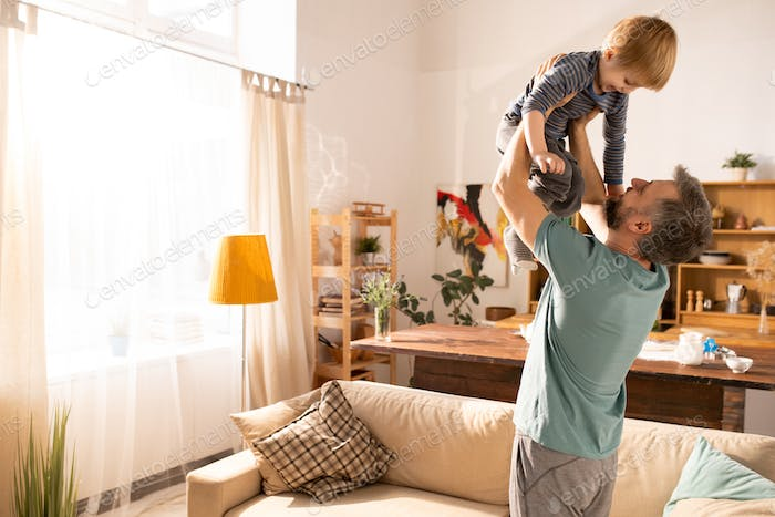 Happy father raising son at cozy home