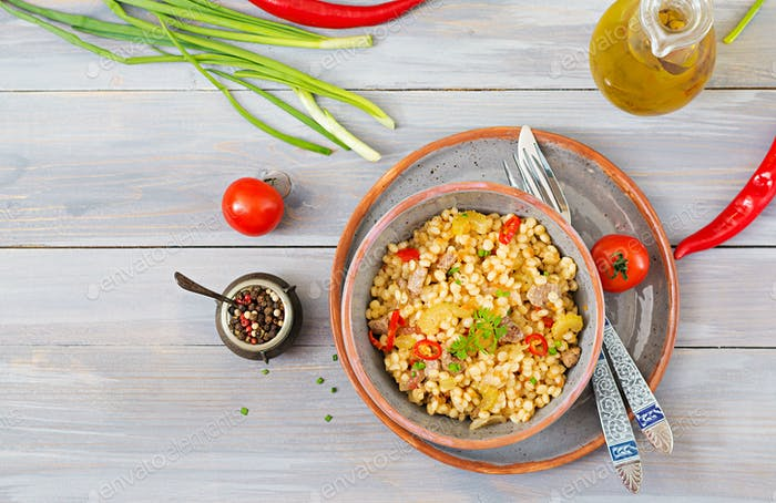 Porridge from Turkish couscous with beef and vegetables. Dietary menu. Top view.
