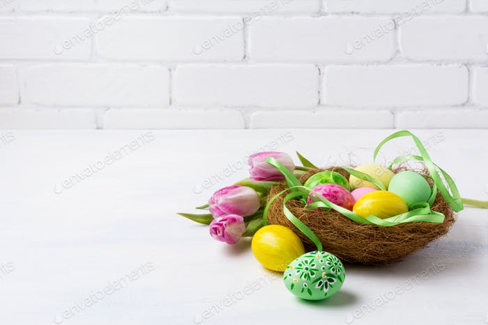Easter green and yellow painted eggs in the nest and pink tulips