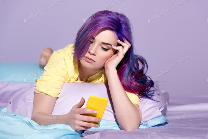 bored young woman using smartphone in bed
