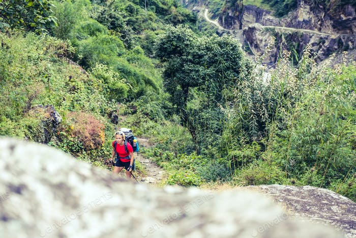 Woman backpacker climbing with backpack in Himalayas, Nepal