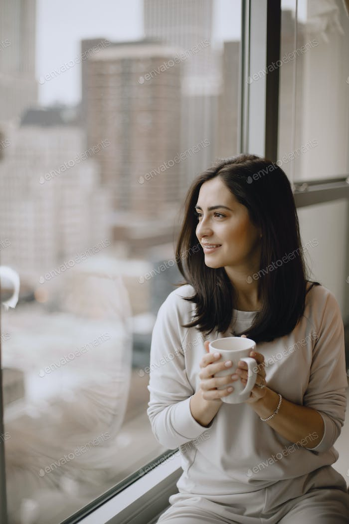 Brunette sitting on a windowsill and drinks a coffee