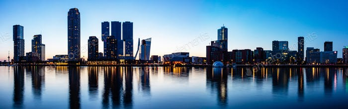 Rotterdam Netherlands skyline night panorama. City towers illuminated, reflections on the wate