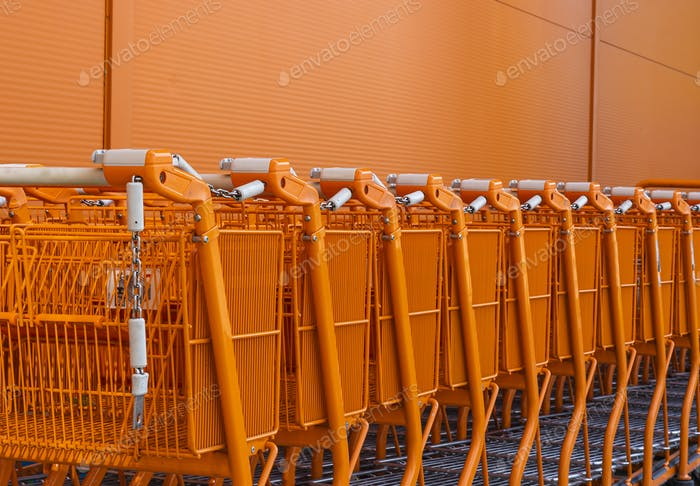 Orange shopping cart stacked by the entrance