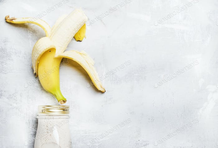 Banana smoothies in a bottle, top view, flat lay