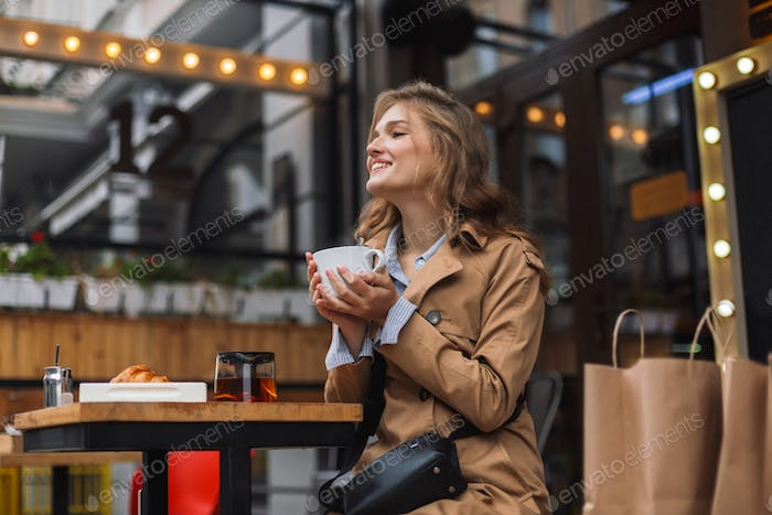 Young attractive woman in trench coat happily looking aside whil
