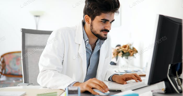 Doctor typing and using his computer