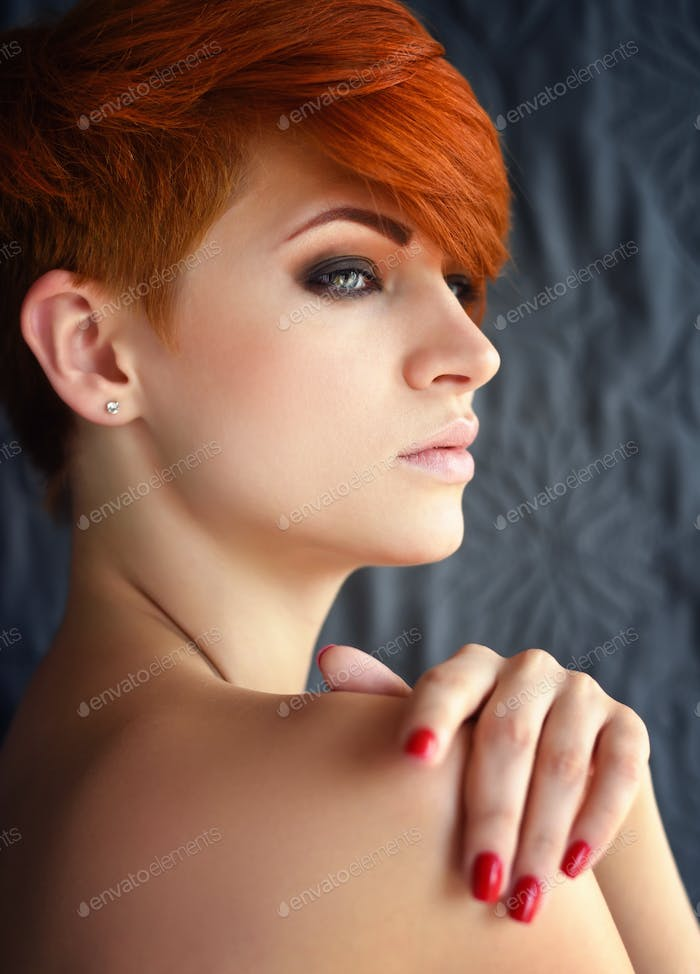 Portrait of a beautiful young red-haired woman with short hair o