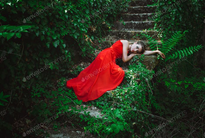 Beautiful woman in red dress lying on the steps of the old stair