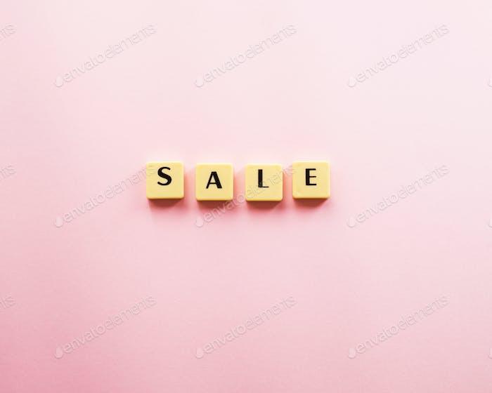 Verkaufswort mit Kunststofffliesen auf rosa