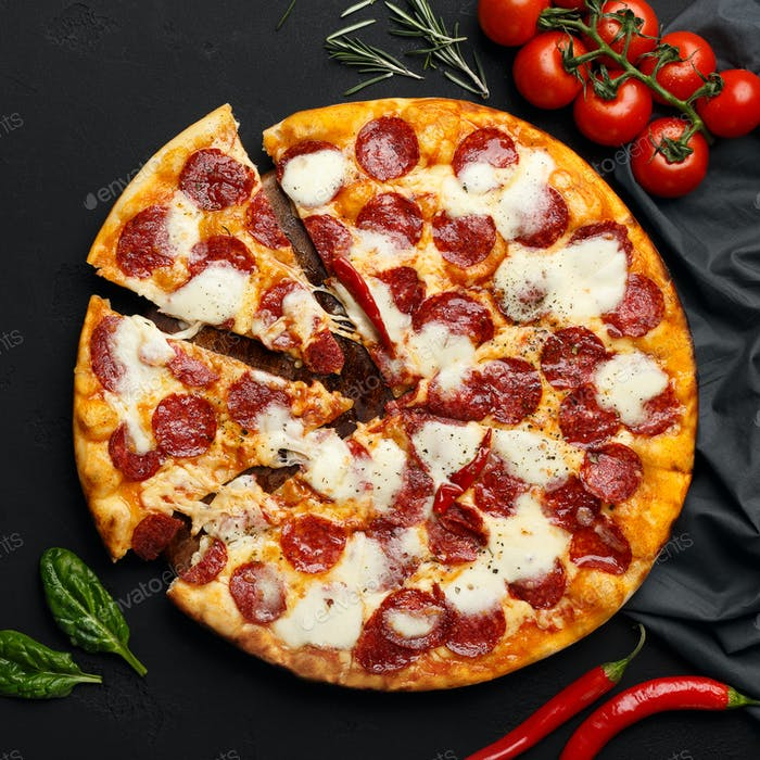 Hot Sliced Pepperoni Pizza On Black Table
