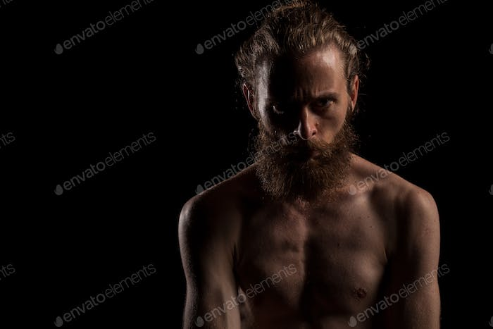 Portrait of bearded cool hipster on black background