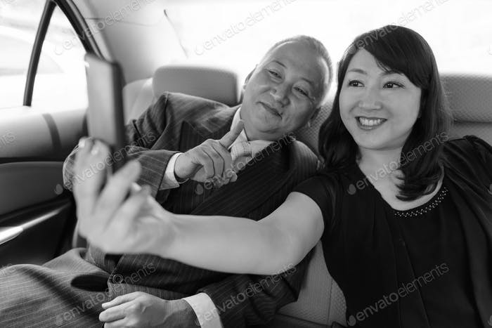 Mature Asian businessman and mature Asian woman exploring the city together