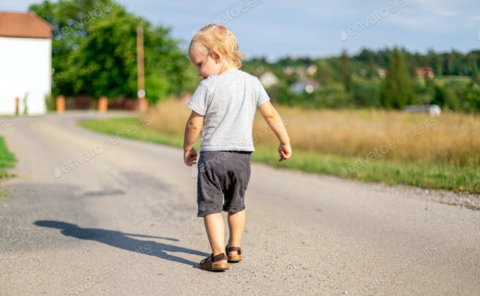 Child boy walking alone on road at countryside