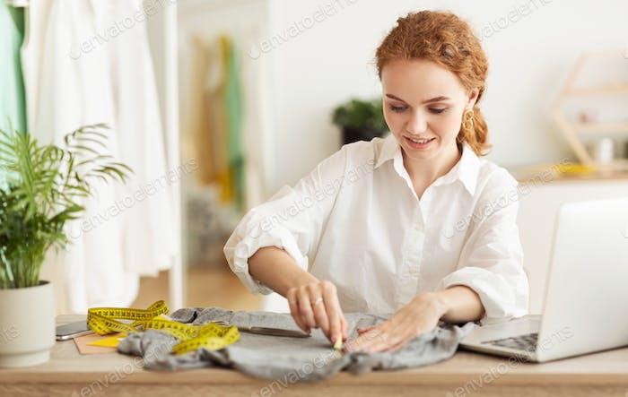 Женщина рисует узоры с мылом или мелом на ткани