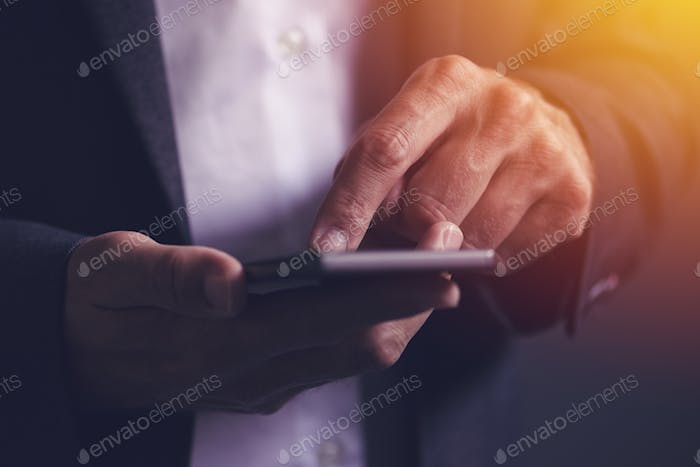 Close up of male businessman hands using mobile phone