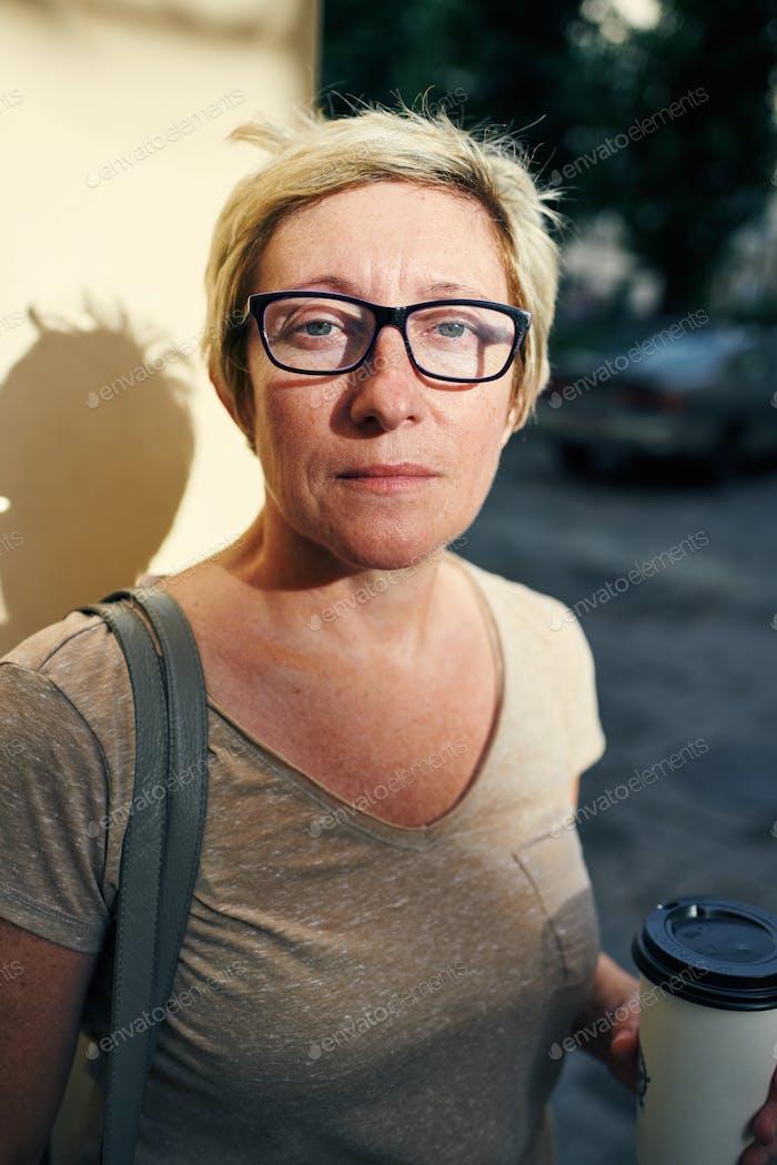 Senior woman with beverage looking at camera