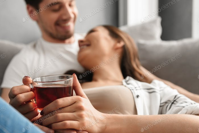 Blurry photo of cheerful couple lying on sofa in flat, while wom