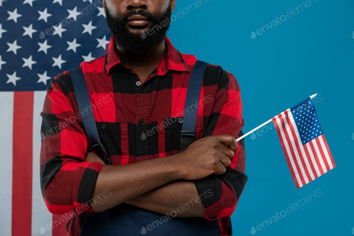 Young bearded repairman of African ethnicity in workwear holding American flag