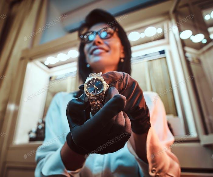 Verkäufer zeigt eine exklusive Herrenarmbanduhr aus der neuen Sammlung im Luxusjuwelier