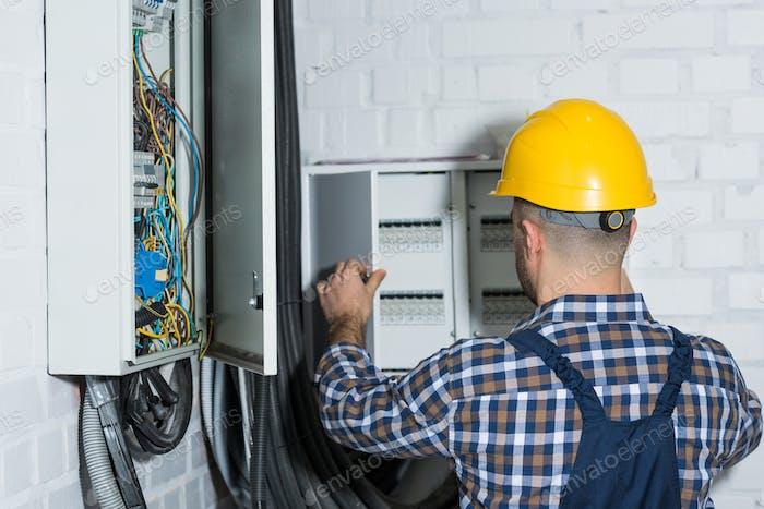 Männlicher Elektriker repariert Stromkreisleitung