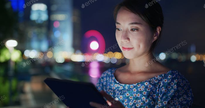 Woman use of tablet computer at night