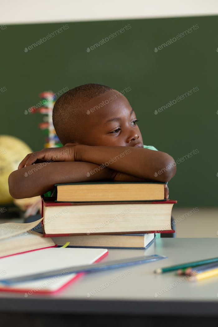 Schoolboy supporting his head on his arms crossed on books at desk in classroom at elementary school