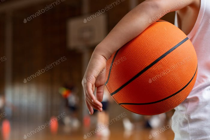 Mixed-race schoolboy with a basketball under his arm standing in basketball court at school