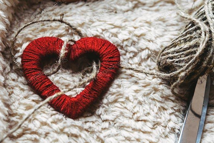 einfaches handgefertigtes Herz auf einzigartigem, gemütlichem Hintergrund mit Faden und Schere