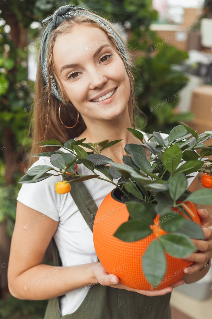 Caucasian woman with homemade tangerine tree in pot