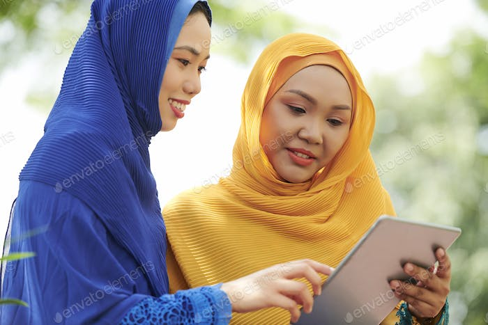 Women in hijabs with digital tablet