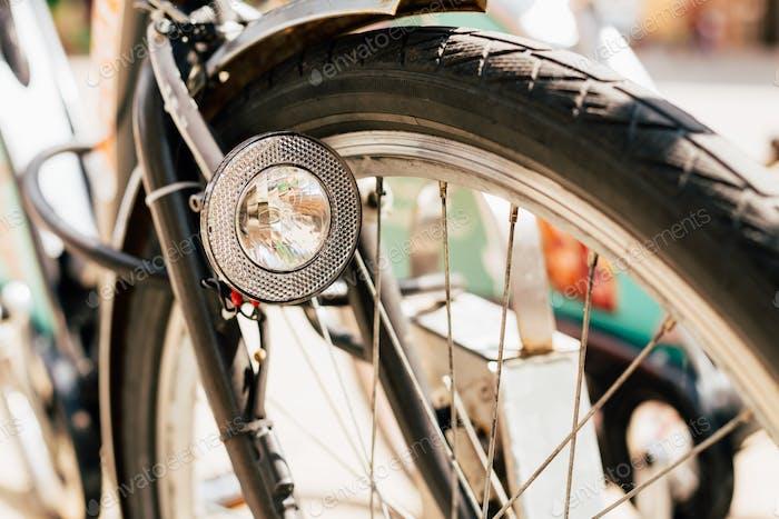 Закрыть до велосипедной фары и колеса велосипеда на улице. Велосипед