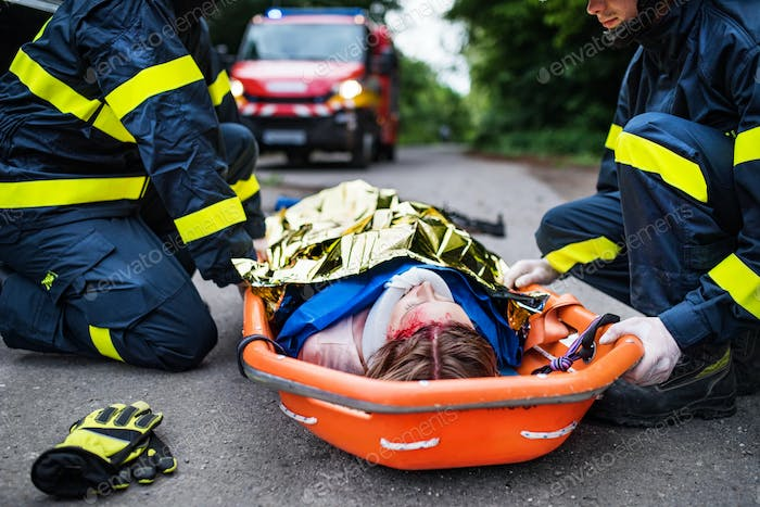 An injured woman in a plastic stretcher after a car accident, covered by thermal blanket.