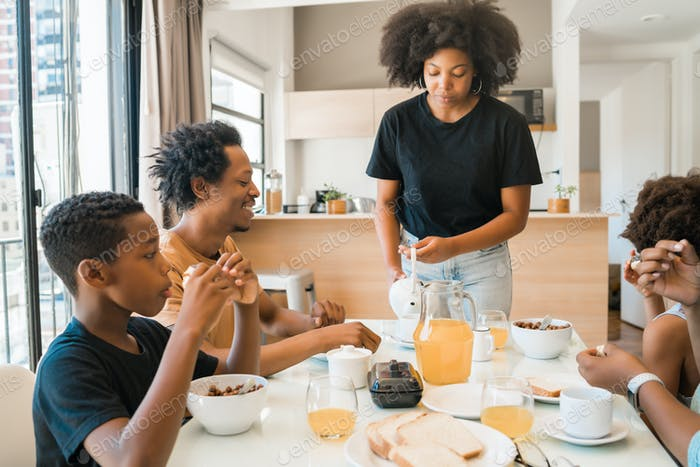 Familie beim gemeinsamen Frühstück zu Hause.