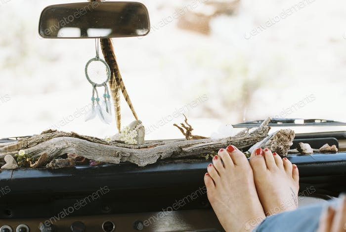 A woman resting her bare feet on the dashboard of a 4x4, on a road trip