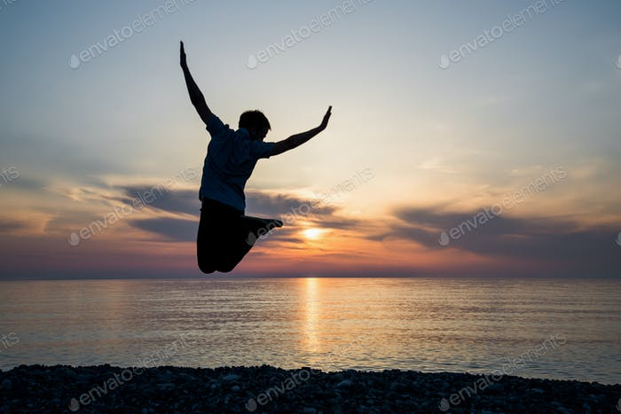 silhouette of teenager jumping in sunset for fun