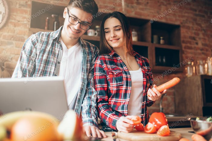 Couple looks at a recipe in laptop, salad cooking