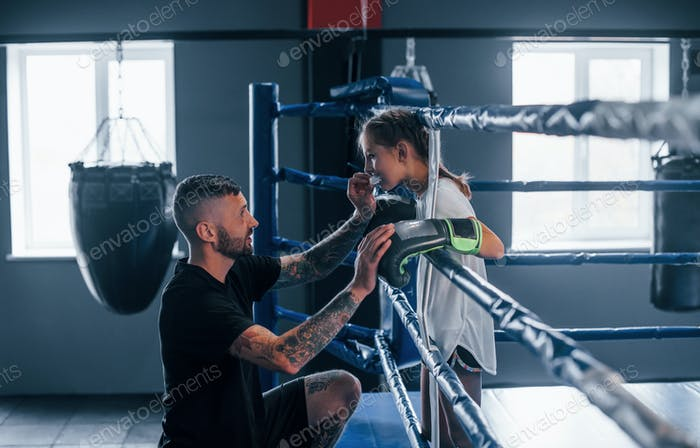 Conception of assistance. Young tattooed boxing coach teaches cute little girl in the gym