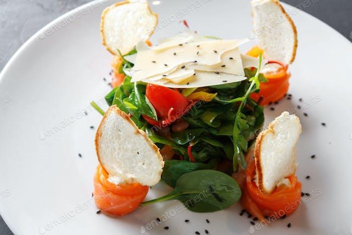 Restaurant dish on white plate on black background, closeup
