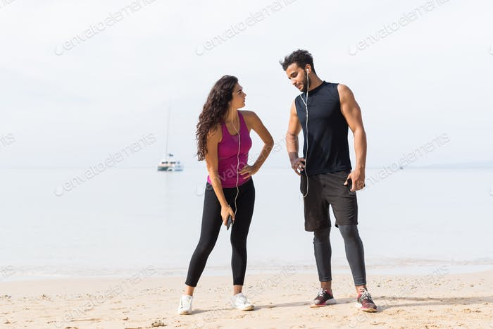 Couple Of Runner Having Rest After Training On Beach Man And Woman Sport Runners Standing Fit Male