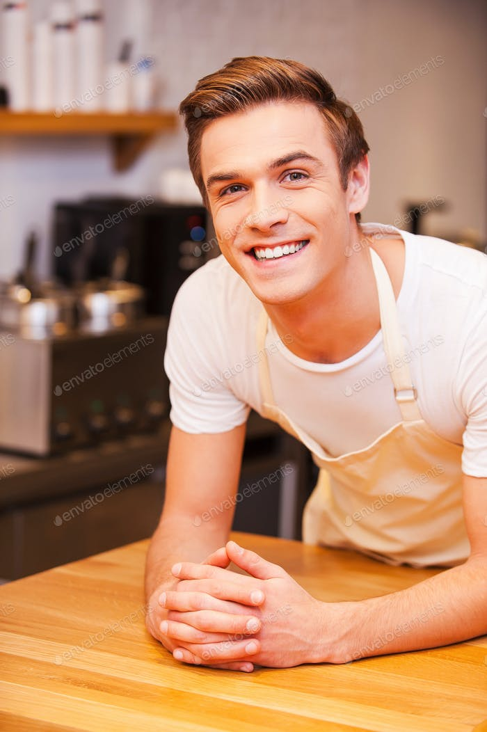 Waiting for customers. Confident young male barista leaning at the bar counter and smiling