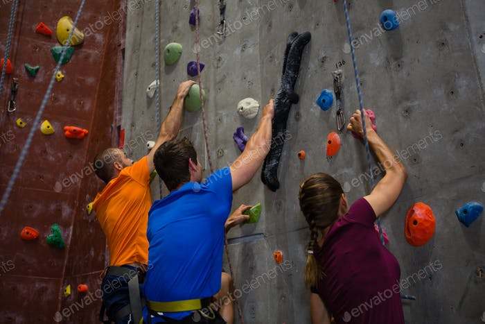 Athletes and trainer climbing wall in gym
