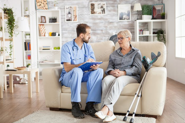 Male doctor with senior woman sitting on couch
