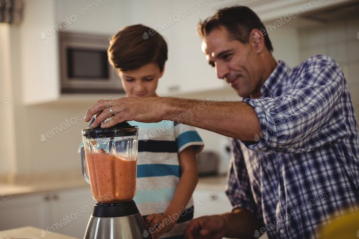 Father and son preparing smoothie in kitchen